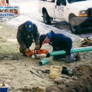 Prepping sewer line pipe for installation.